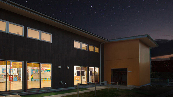 夜になって窓の中が明るくなっている保育園の園舎