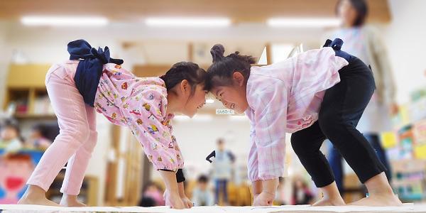 相撲の立ち合いでにらみ合う女の子二人